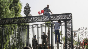 Tunisian soldiers guard the main entrance of the parliament as demonstrators gather outside the the gate in Tunis.