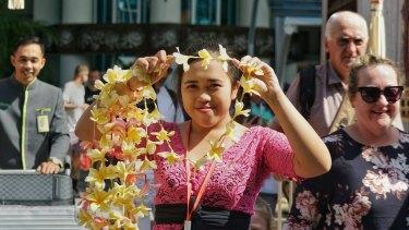 Wayan Ani passes out frangipani necklaces to visitors arriving at Bali Ngurah International Airport.