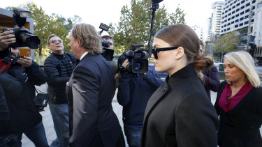 A press pack surrounds Belle Gibson as  she makes her way into court.