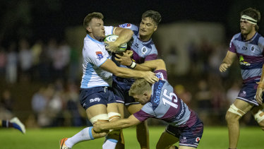 Waratahs back-rower Jack Dempsey is tackled by Reds backs Jordan Petaia and Bryce Hegarty.