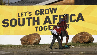 Schoolchildren walk home past an election mural for the ruling African National Congress (ANC) party in Johannesburg, South Africa.