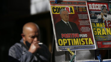 """A newspaper's front page carries the Spanish headline """"Positive but optimistic"""" for the story about Mexican President Andres Manuel Lopez Obrador having COVID-19."""