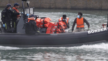 A Border Force vessel brings a group of migrants into the port city of Dover, England.