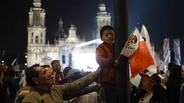 A child holds a Mexican flag as supporters of presidential candidate Andres Manuel Lopez Obrador celebrate his victory, on Mexico City's Madero main square, the Zocalo, on Sunday.