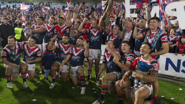 Cock-a-hoop: Sydney Roosters players celebrate in front of their faithful after their grand final victory.