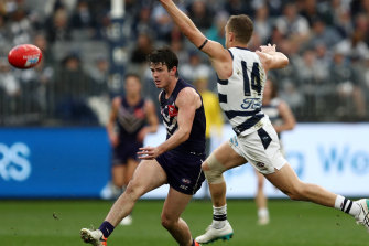 Andrew Brayshaw of the Dockers kicks past Joel Selwood of the Cats.