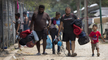 Honduran migrants leave the shelter they were staying at after receiving temporary permission to remain in Mexico.