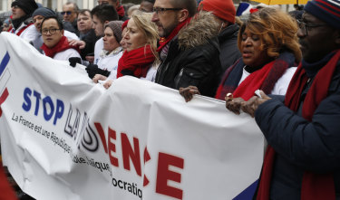 Protesters carry an anti-violence banner through the streets of Paris on Sunday.