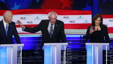 Democratic presidential candidate Senator Bernie Sanders, centre, gestures towards former vice-president Joe Biden as Kamala Harris talks.