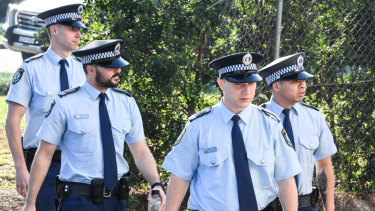 Police arrive at the NSW Coroners Court on Friday.