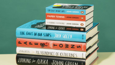 Mini book versions of works by John Green compared with their full-size counterparts.