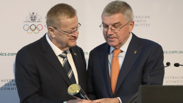 Passing the baton: Bach is presented with the Australian Olympic Committee President's trophy by AOC president John Coates.