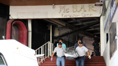Workers from a forensic service carry the body of a man who was killed by gunmen inside a bar in Acapulco, Mexico.