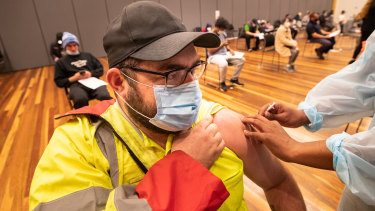 A man rolls up his sleeve to get jabbed at a vaccine clinic in Hoppers Crossing.