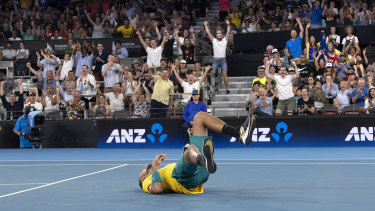 Nick Kyrgios falls to the ground after winning his singles match.