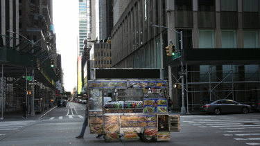 A food truck vendor pushes his cart down an empty street near Times Square in New York. Mayor Bill de Blasio has ordered bars, restaurants and cafes to shut down.