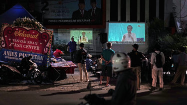 People watch last month's second presidential debate on the street in Jakarta.