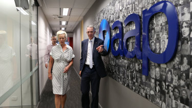 Campbell Reid (right) and Emma Cowdroy walk away after the closure announcement at AAP head office in Sydney.