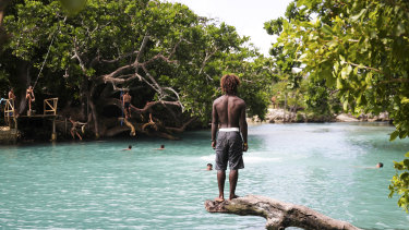 People swimming at the Blue Lagoon on Efate Island in Vanuatu with the rope swing visible on the left side.