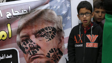 A boy next to a desecrated poster of US President Donald Trump during a rally  to condemn the killing of Iranian Revolutionary Guard General Qassem Soleimani.