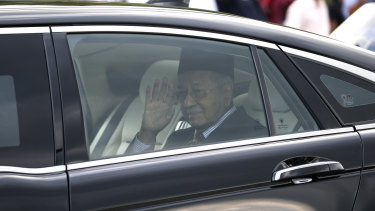 Mahathir Mohamad waves after being granted an audience with the Malaysia's King Sultan Abdullah Sultan Ahmad Shah at the National Palace in Kuala Lumpur.