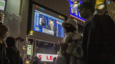 People walk through the Shinjuku area as the Prime Minister is seen on a large screen announcing the state of emergency.