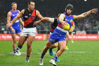 Caleb Daniel gets a kick away in the wet.