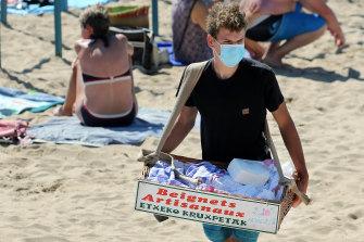 A vendor sells doughnuts on the beach in Saint Jean de Luz in south-western France.