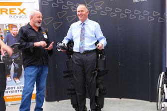 Rex Bionics chief technology officer Richard Little puts New Zealand Prime Minister John Key through his paces during a 2016 visit