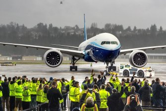Boeing employees and family members cheer the 777X at Boeing Field in Seattle after it completed its maiden flight.