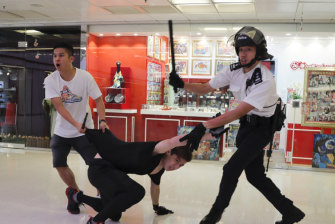 Police detain a young man in Amoy Plaza.