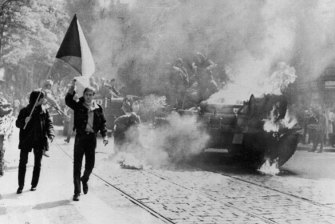 Defiant young Czechs carrying their country's flag past a burning Soviet tank on a street in Prague.