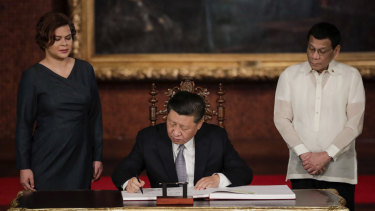 Chinese President Xi Jinping signs the guest book as Philippine President Rodrigo Duterte and daughter Sara Duterte look on last year.