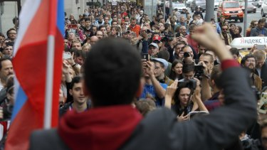 Russian opposition candidate and activist Ilya Yashin, back to a camera, speaks to a crowd during a protest in Moscow.