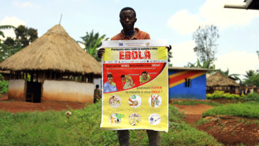 A man displays an Ebola information leaflet for residents in Mangina, Democratic Republic of Congo.