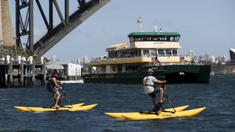 Mark Sedgman and Dan Westwood ride bikeboats on Sydney Harbour.
