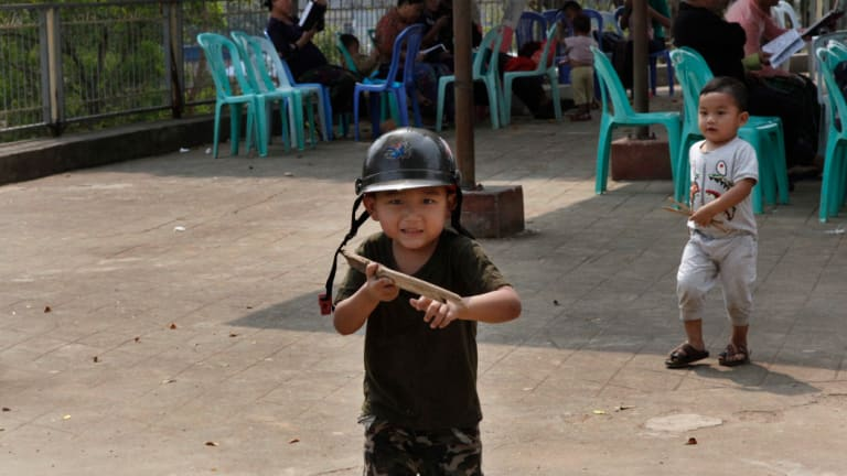 Five-year old Zai Zin Awng, with a toy gun imitates a Kachin rebel as he plays outside a Baptist church in Laiza, the headquarters of the Kachin Independence Army in northern Kachin State, Myanmar.