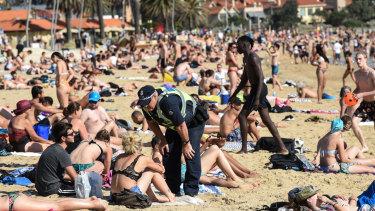 Police speak to beachgoers at St Kilda on Thursday.