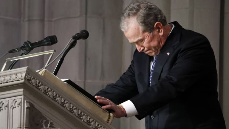 Former US president George W. Bush pauses while speaking.