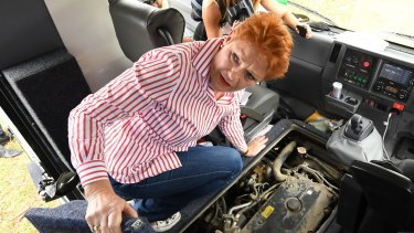 One Nation leader Pauline Hanson is seen inspecting the engine bay of the Battler Bus.