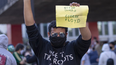 "An anti-government demonstrator holds a sign that reads in Portuguese ""Our brother George Floyd,"" during a protest in Sao Paulo on Sunday."