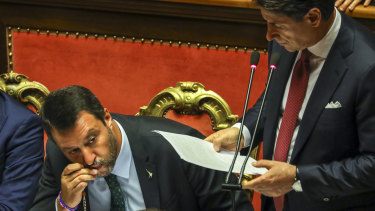Matteo Salvini, left, kisses his rosary beads as Giuseppe Conte addresses the Senate.