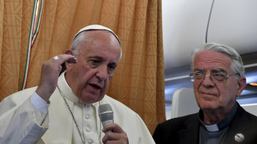 Pope Francis, flanked by Vatican spokesman Federico Lombardi, right, talks to journalists during a press conference he held on board the airplane on his way back to the Vatican in 2016.