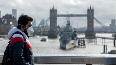 A man wearing a mask walks over London Bridge in central London with the Tower Bridge behind.