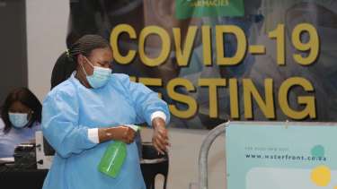 A healthcare worker sanitises her hands before conducting COVID-19 tests at a drive-through testing station in Cape Town, South Africa.