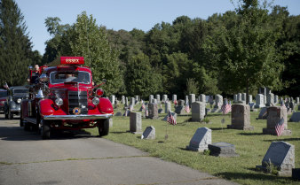The coffin of Joe Heller is brought to the cemetery on the Essex Fire Department's historic truck in Essex, Connecticut.