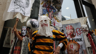 British Fashion designer Vivienne Westwood, centre, with her head covered, poses for photos during a protest to support Julian Assange outside the Central Criminal Court Old Bailey in London.