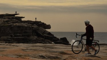A cyclist looks at people on cliffs at Clovelly Beach.