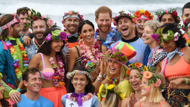 Britain's Prince Harry and Meghan, the Duchess of Sussex, pose at Bondi Beach with surfing community group, known as OneWave, who raise awareness for mental health and wellbeing.