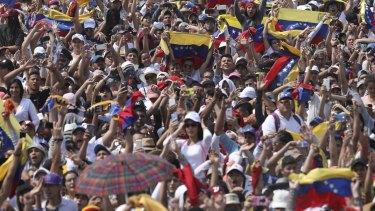 Concert goers unfurl their Venezuelan flags during the Venezuela Aid Live concert on the Colombian side of the Tienditas International Bridge near Cucuta, Colombia.